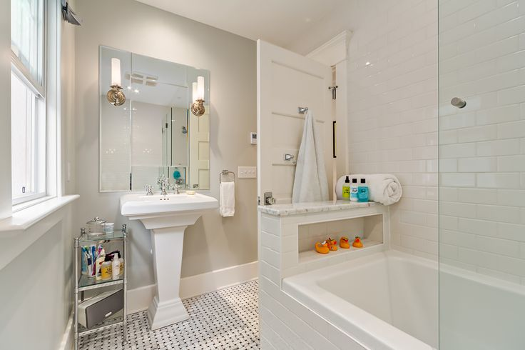 The main bathroom is stunning in all white, from the basket weave tiled floor to the white subway tiles installed on the tub and shower surrounding walls, to the wood trimwork painted white. Marble tops the tub shelf. Fixtures are classic shiny chrome. The entire look is fresh, clean and bright.