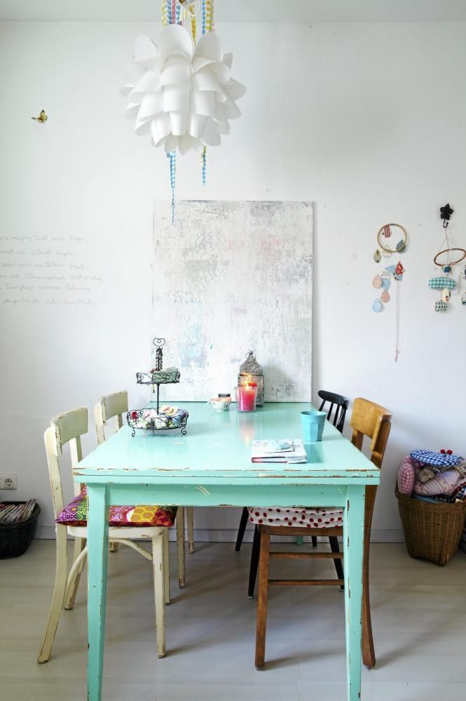 Spisebordet er malt i sterk turkis, som så har blitt pusset litt i hjørner for å skape et gammelt preg. Fra den moderne taklampen henger det fargerike perlekjeder i plast. Vegger, tak og gulv er holdt i hvitt.