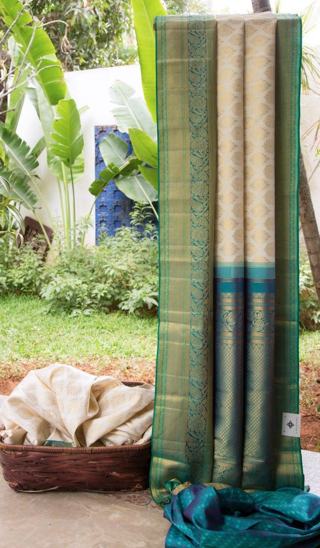 Ivory kanchivaram silk has gold zari bhuttas all over. The border is in sea green and teal with a gold zari weave, while the pallu is in teal with intricate gold zari weave adding a traditional cha...