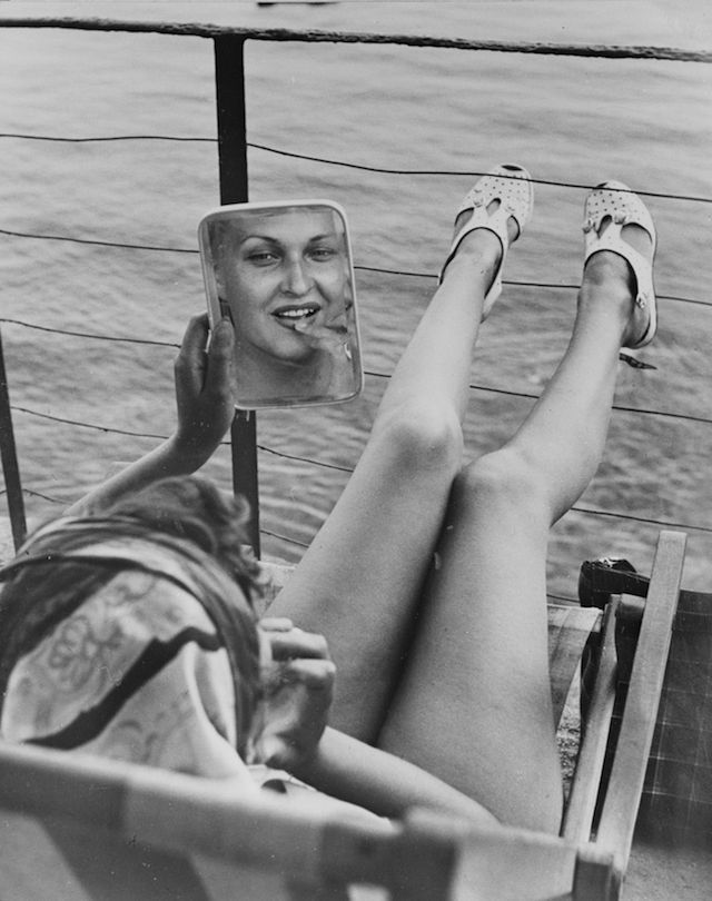 A young woman looks herself  into a mirror while sunbathing on a boat at Portofino, Italy, 11 August 1949 [ Keystone / Getty Images ]