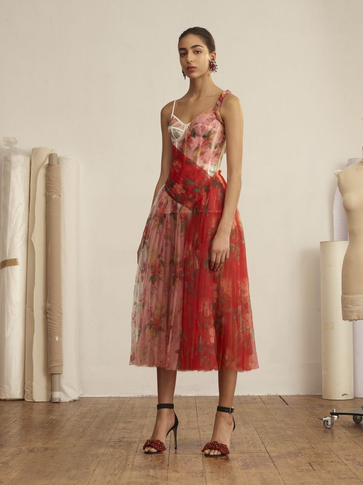 Botanical florals are printed onto a sheer organza sunray pleated corset dress in shades of rose, lust red and coral. The dress is worn with black silk satin sandals embellished with a lust red crystal encrusted bow. Both from the Alexander McQueen Spring/Summer 2018 pre-collection.