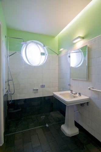Ducha con shower door y mur con cerámicos blancos y parte superior pintada verde agua. Lavamanos blanco con pedestal y piso de piedra pizarra, gris oscuro (casi negro).