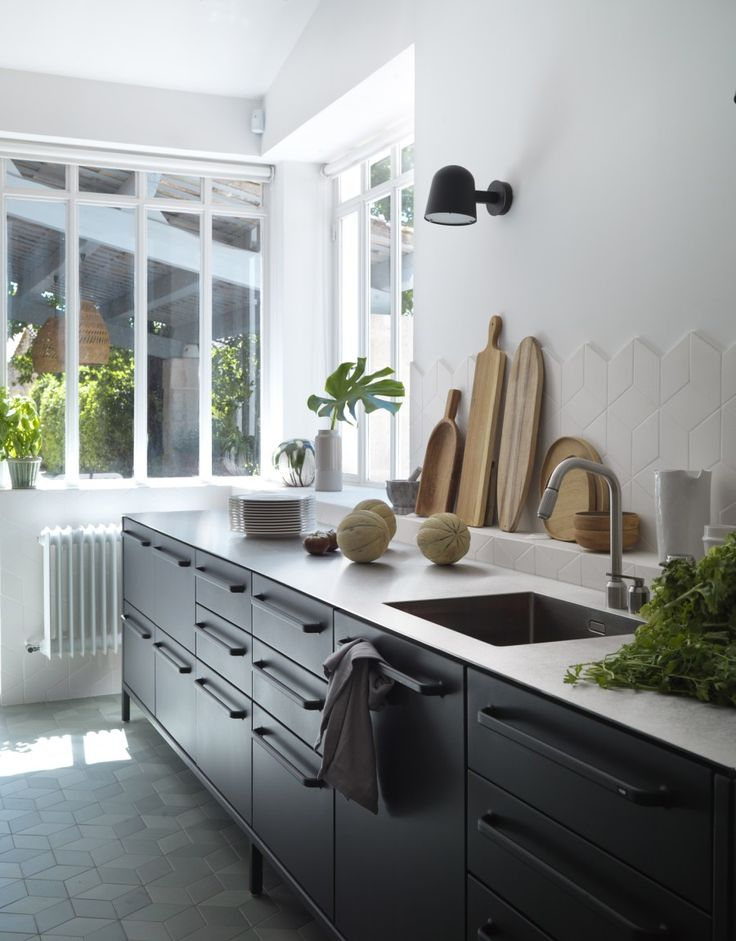 Light filled Scandinavian kitchen with black units. Organic cotton tea towels from VIpp