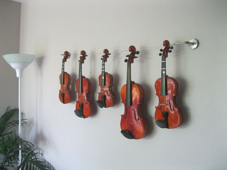 We had a space on a wall in our living room for which we couldn't find a picture so we gathered up the different sized violins our son graduated through and hung them from their scrolls on a wire hanging kit from IKEA. We were going to fix the violin with the strings protruding out but decided to leave it like it is.