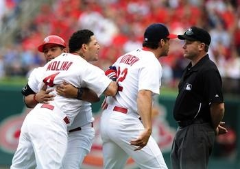 assistant hitting coach Bengie Molina holds back his younger brother as manager Mike Matheny argues with umpire Clint Fagan after Molina and Matheny were ejected from the game during the third inning against the SF Giants at Busch Stadium. Cards lost 4-2. 6-02-13