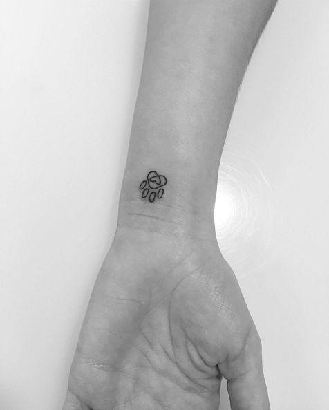 Lovely paw print wrist tattoo by Jon Boy