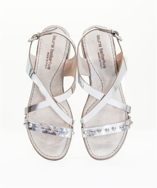 Shine this summer in the Newport, a silver metallic flat sandal with stud accents across the foot. Flattering criss-cross straps with adjustable slingback. Made in Italy.