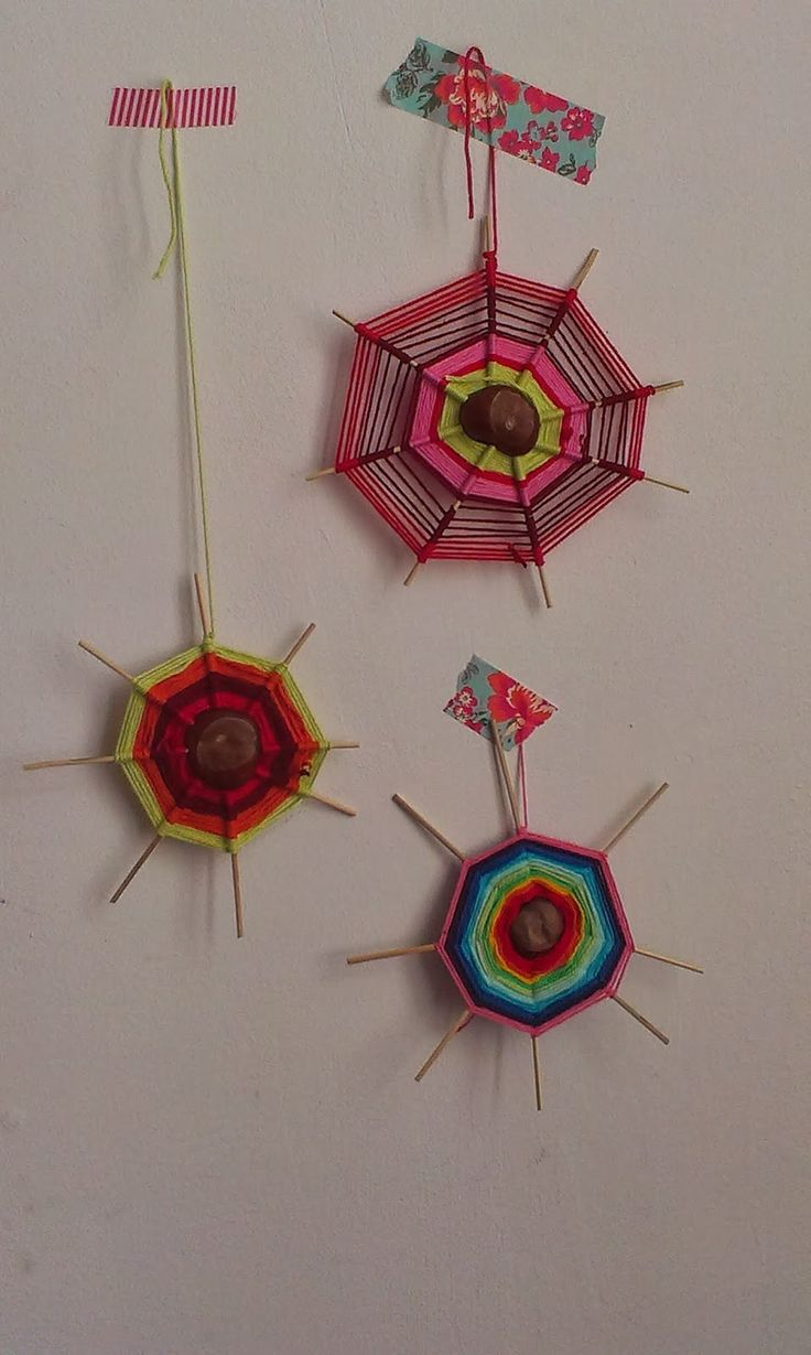 Vrolijk gekleurde spinnenwebben van kastanjes, lange saté-prikkers en gekleurde wol