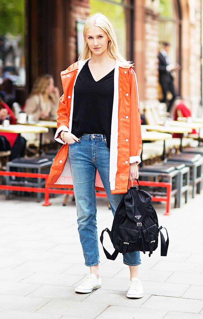 Kristin Zetterlund in an orange coat, black t-shirt, jeans, and white sneakers