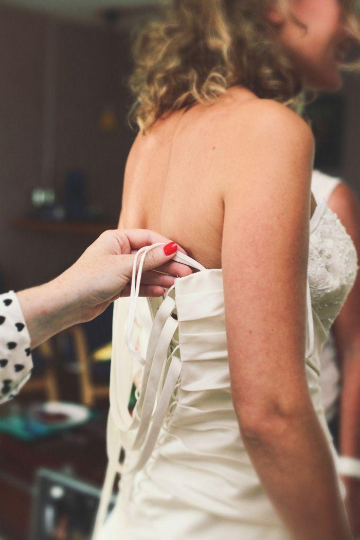 de trouwjurk van de bruid wordt dichtgeknoopt
