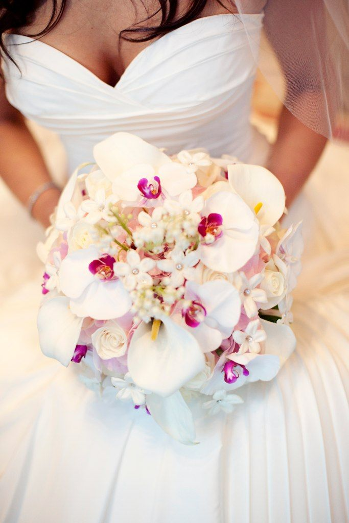 Stunning bridal bouquet of phalenopsis orchids, stephanotis, and spray roses. Love the placement of the orchids and their hot pink lips!