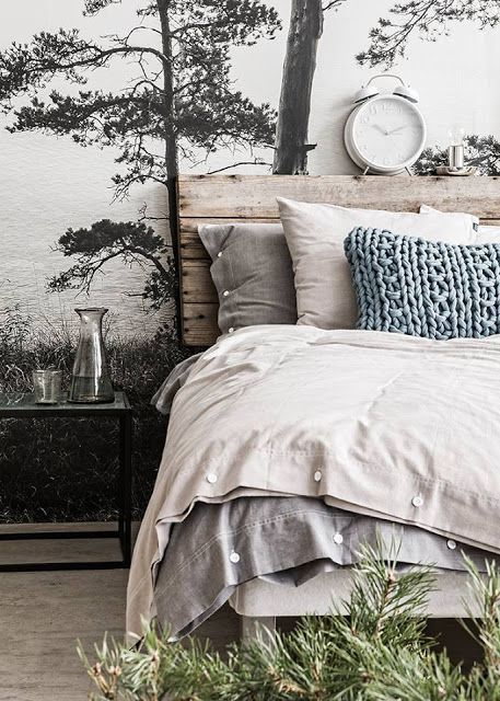 Cette chambre au style scandinave apporte la nature avec elle en utilisant des matériaux naturels : Tete de lit en bois brut, coussin en laine tricotée, linge de lit et drap en lin ainsi qu'un papier peint effet trompe l'oeil avec un dessin de foret et d'arbres