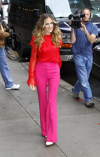 SJP pairs pink pants with a red top.
