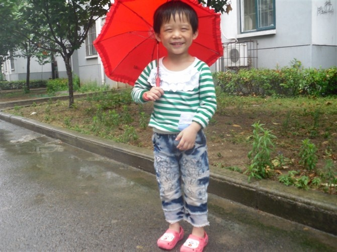Even a rainy day can't keep a smile off Honor's face as she heads to school in Anhui province.
