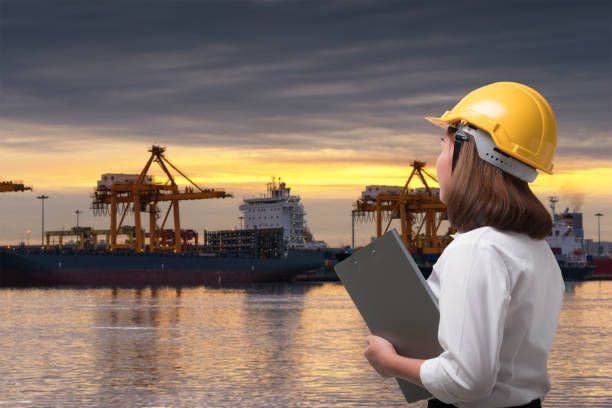 female engineer wearing safety helmet in shipping port