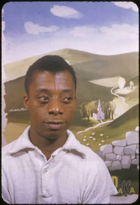 James Baldwin posing in front of an American Airlines poster. (1955) by Carl Van Vechten