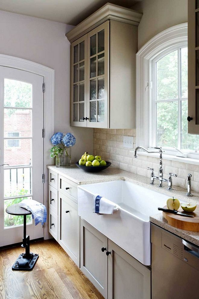"""Kitchen sink is a 36″ wide farm sink by Franke.  The backsplash is an Imperial Cream Limestone """"Durango Cushioned"""" 3×6 from Artistic Tile and the countertop is Ice Stone """"Aurora Gold"""".  Wentworth, Inc."""
