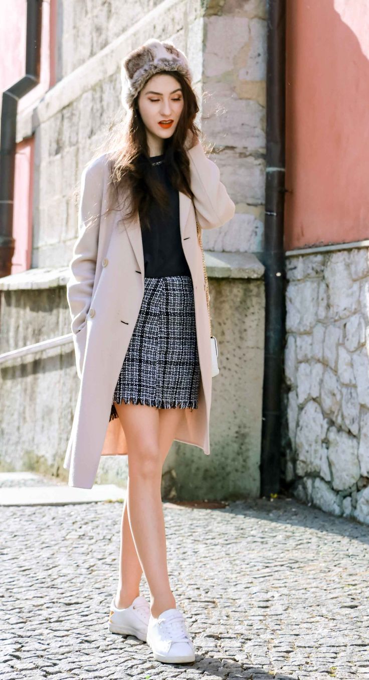Fashion Blogger Veronika Lipar of Brunette from Wall Street dressed in white sneakers from Diesel, black and white plaid tweed mini skirt from Storets, black silk blouse from Juicy Couture, off-white double breasted wool coat from MaxMara, faux fur headband, chain strap shoulder white bag, blue leather gloves on the street in Ljubljana