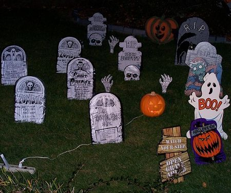 create a scary outdoor halloween decoration depicting a cemetery with tombstones