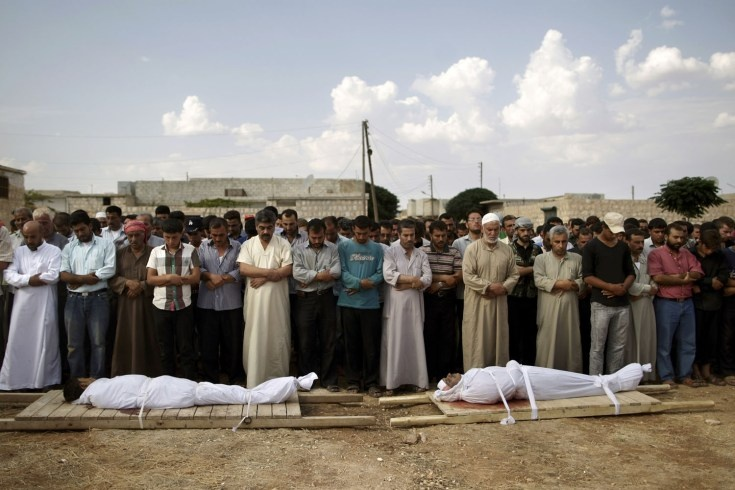Sept. 11, 2012. Relatives and mourners of Abdullah Alrayzar, 23, left, and Mohammed Abdul Samee, 35, pray during a funeral for four men, who were killed in a government airstrike in Marea, on the outskirts of Aleppo, Syria.