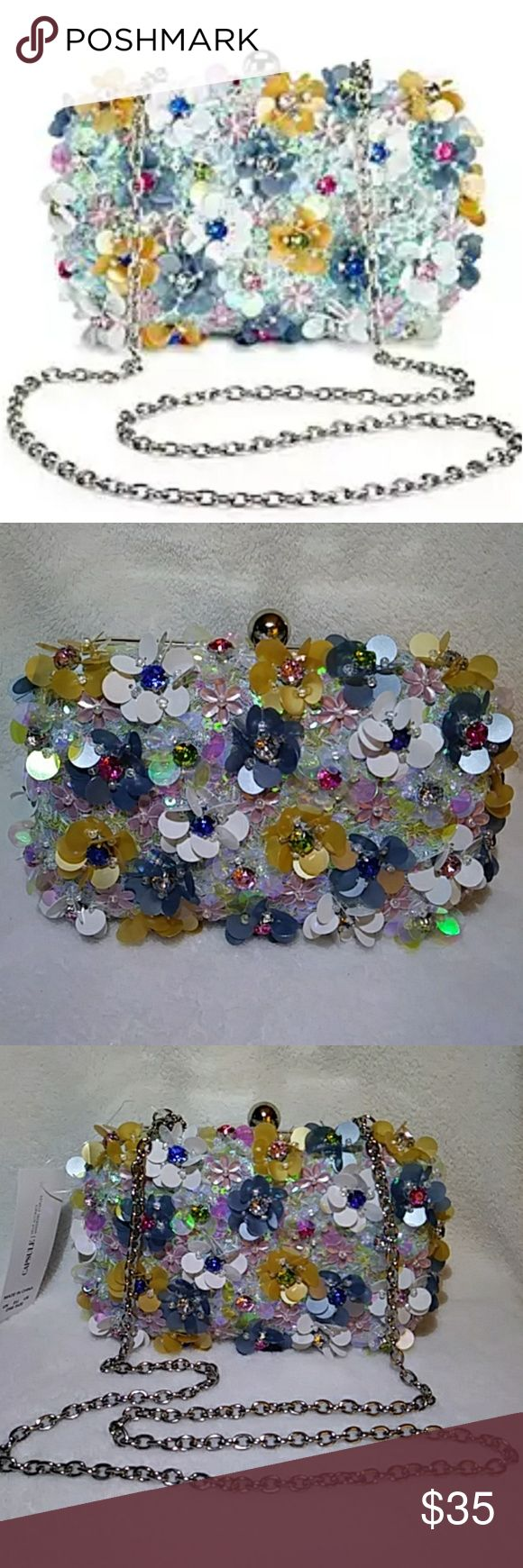"""Capsule Floral Embellished Clutch Floral 3D embellished clutch bag. Has a clasp fastening and chain strap. Chain can very neatly be put inside clutch if you choose to carry it by hand. Stunning iridescent and multi- colored sequins and colored beads cover this bag all over the front. 1 slip pocket inside. Approximately 4"""" x 6.5"""". A very unique 3D clutch you can carry day or night! Has two small imperfections, barely noticeable as you can see in pictures 3 & 7 Had to have happened during…"""