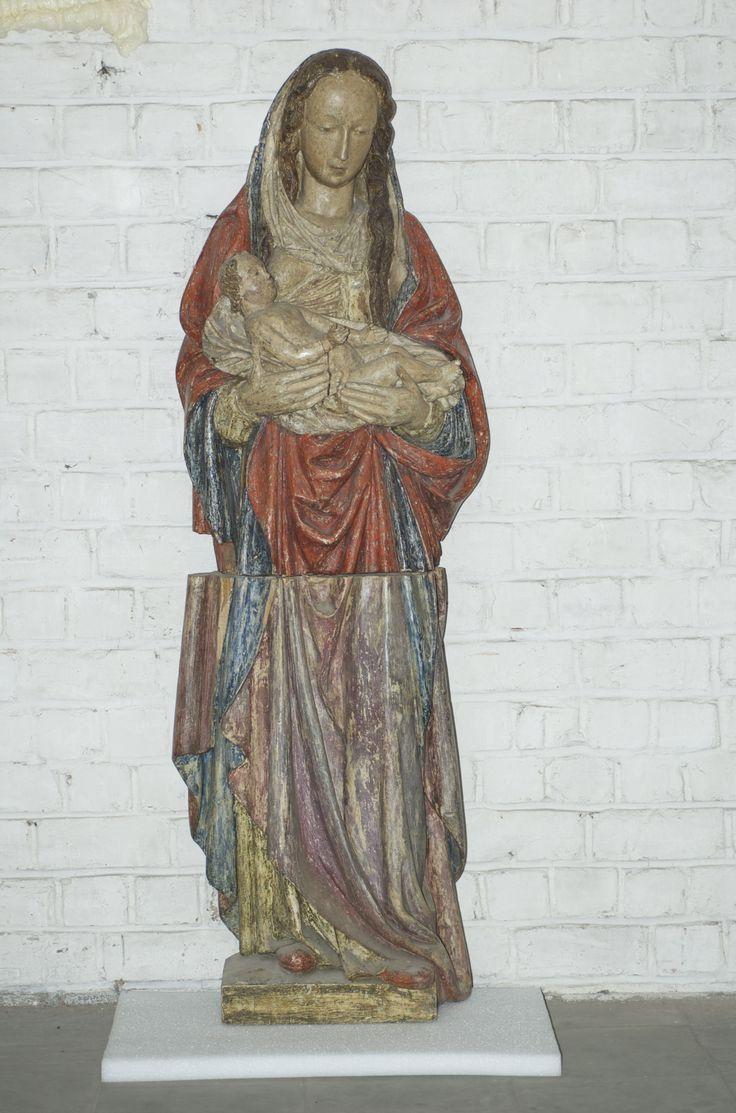 Sokkel met fotomontage  Madonna met Kind gezeten op haar rechterarm. mantelzoom van Maria: ma... gracia.... piena. Maria staat recht op een afgerond voetstuk. In de rechterhand draagt ze de schrijlings zittende Jezuskind dat, getooid  in een lange blauwe tunica, het rechterarmpje uitstrekt. Maria's gelaat wordt gekenmerkt door  een hoog voorhoofd, nauwelijks geopende ogen, een sterk getekende mond met diepe mondhoeken en vooruitstekende kin. De lange haarlokken worden boven het hoofd…