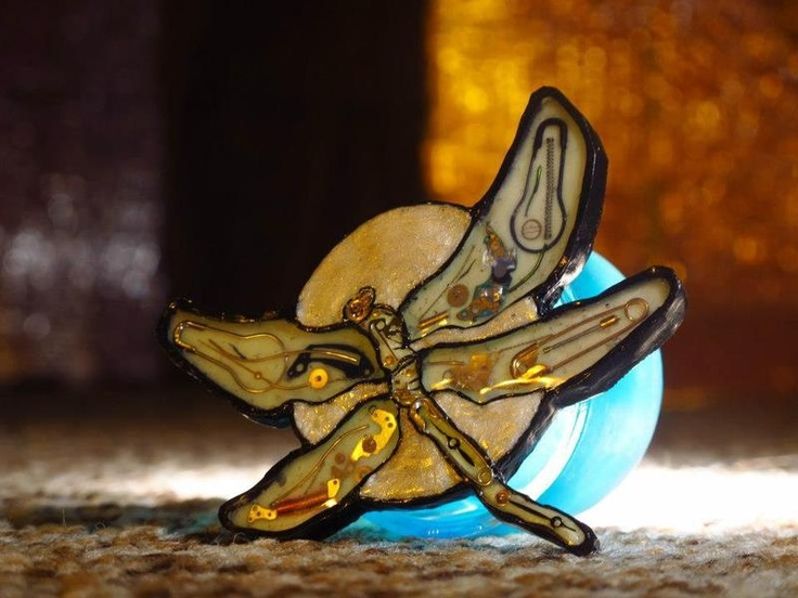 Hand sculptured steampunk brooch, one piece only. Polymeric clay, liquid glass with embedded mechanical parts. It glows in the dark.