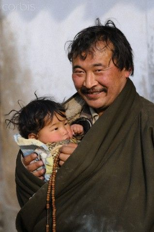 Tibetan father and child at the Monastery of Rongwo, Qinghai, China. Rongwo Monastery also known as Longwu in Chinese is a Tibetan Buddhist Monastery. It was founded in the early 13th century. This is a mother monastery of 35 other monasteries in the region.