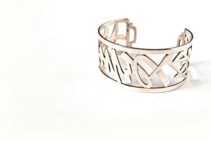"""Bracciale in argento traforato con la scritta in caratteri cinesi """"Amore costante""""."""