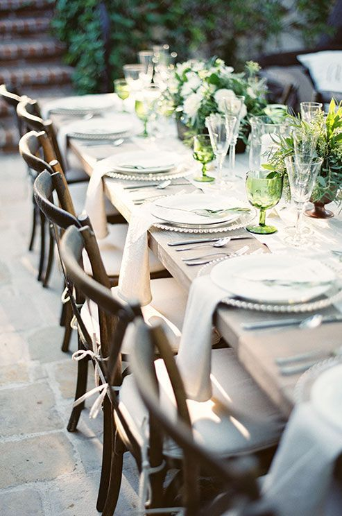 Casual wooden chairs punctuated with white cushions juxtapose chic chargers and silver cutlery.:
