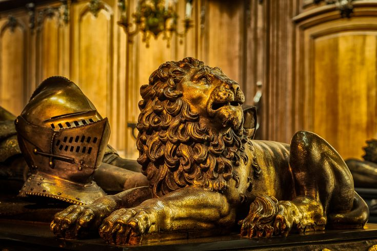 A ornately carved statue of a lion on the tomb of Charles the Bold in the Church Of Our Lady, Brugge, Belgium.