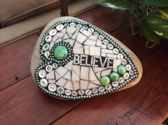 This Mosaic Stained Glass Garden Rock will make a great addition to your garden. It is made with stained glass, glass beads, buttons, blue beaded necklace, a Believe pin, ball chain and I use epoxy grout for outdoor durability. It measures 11 x 8 x 4 inches.