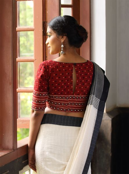 Red three quarter sleeved blouse with black and white cotton saree