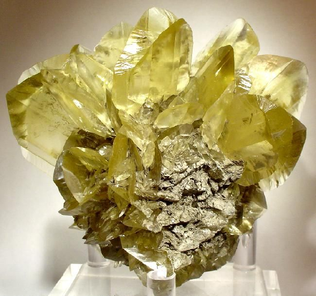 Gypsum (Var: Selenite), CaSO4·2H2O, Red River Floodway, Winnipeg, Manitoba, Canada. Dimensions: 9 x 8 x 5.8 cm. Ten beautiful, transparent and lustrous, fish-tail twinned, golden-amber selenite crystals to 3.7 x 3.3 cm sitting on the crest of a ball of smaller selenite crystals. This beautiful piece is nearly pristine. Copyright: © Rob Lavinsky
