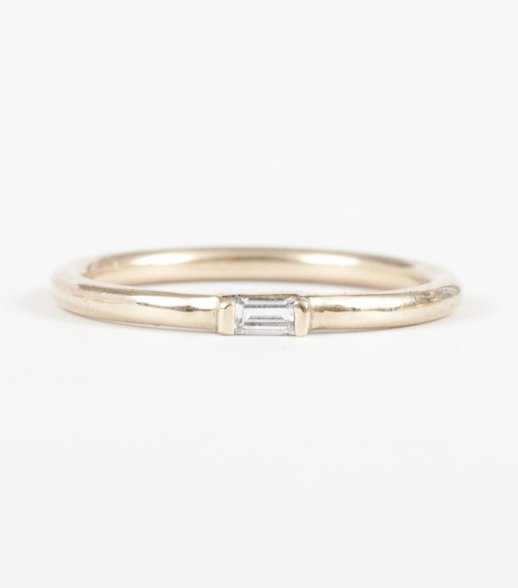 Catbird's sparking white, baguette cut diamond tucked inside of a 14k gold half round band.