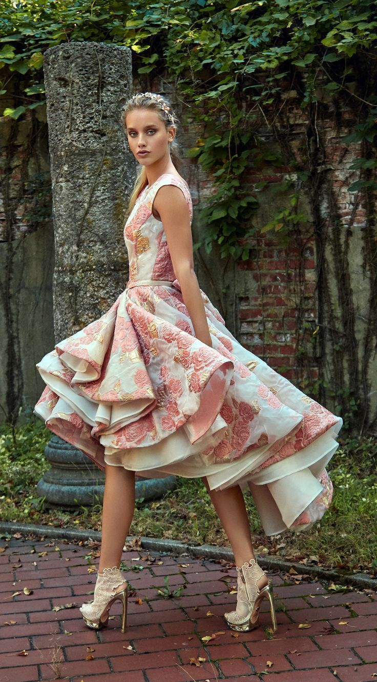 Tailored and short high-low dress with a very voluminous skirt, made of light Orange blossom sheer brocade with touches of gold and a circular hem. A new approach to wedding gowns.