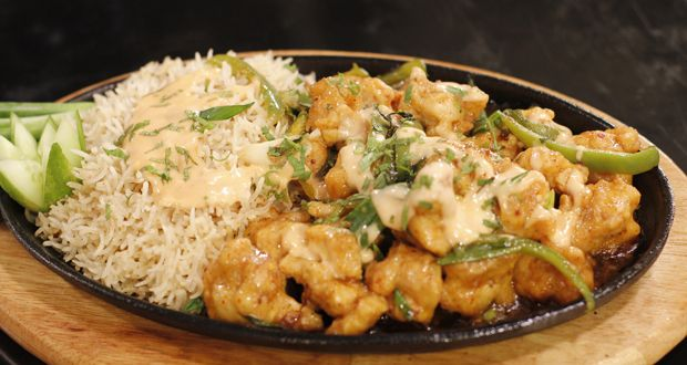 Chicken Sizzler with Garlic RiceIngredients:Chicken (½ inch cubes) 300 gms Vinegar 1 tbspSoy sauce 1 tbspSalt ¼ tspBlack Pepper ¼ tsp Ingredients for batter:Egg 1Flour 2 tbspCorn flour 3 tbspBaking powder ½ tspSalt ½ tspCrushed red pepper ½ tspBoiled rice ½ kg Salt 2 tbsp Mayonnaise 4 tbspSwe