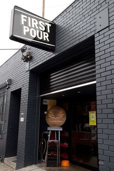 melbourne cafes cafe has black brick walls and a large garage looking door that makes the cafe seem like its in a car garage.