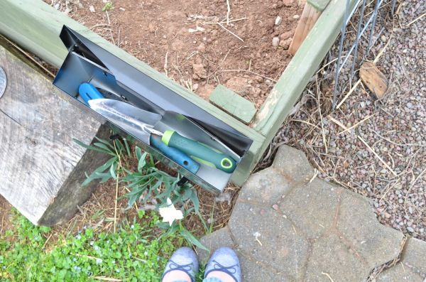 hang up a cheap mailbox on the side of your raised bed to hold small garden tools. genius!