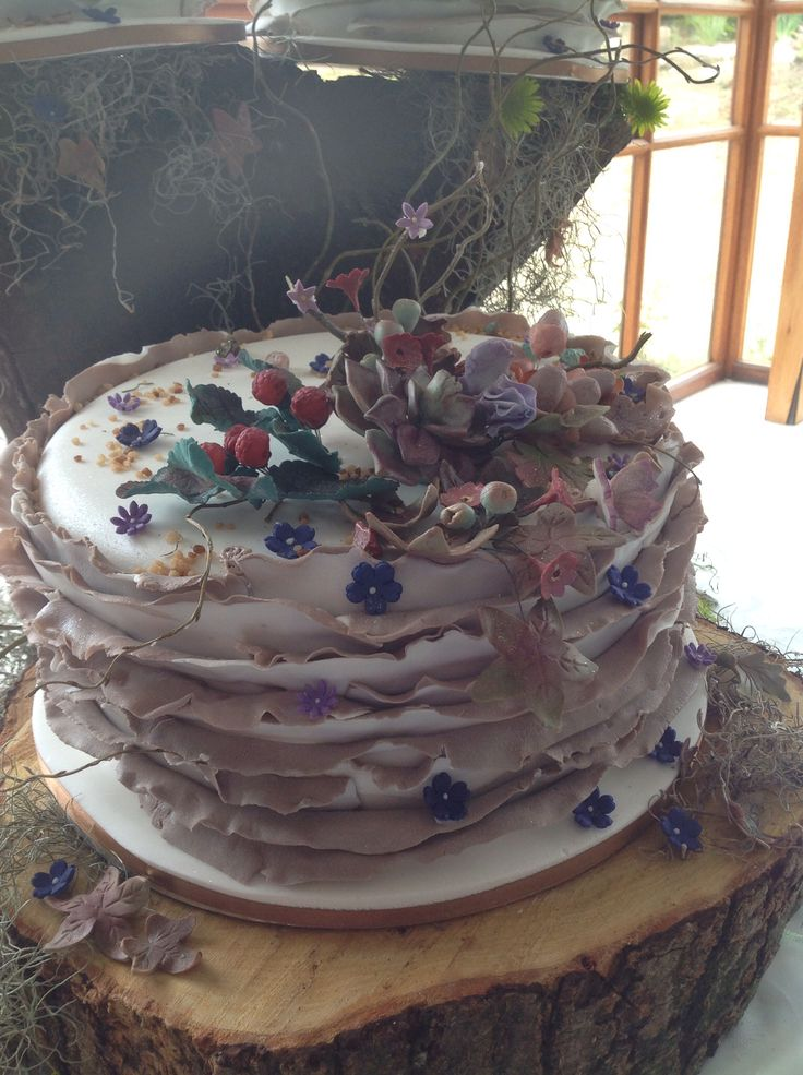 Forest themed wedding cake, with wild berries, acorns and wild flowers.