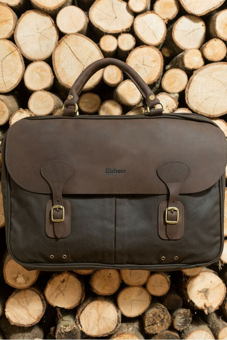 The Barbour Briefcase features a waxed leather outer with signature embossed branding. Two pouches to the front secured with metallic buckles along with an internal mesh pocket with press stud closure. Smooth top handles and a removable shoulder strap complete.