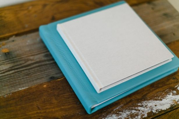 """KISS Book in """"Tusk"""" Linen - a soft ivory textured linen (top) /// KISS Book in """"Tiffany"""" Leather - a summery aqua blue leather. (Photo by Elisabeth Carol)"""