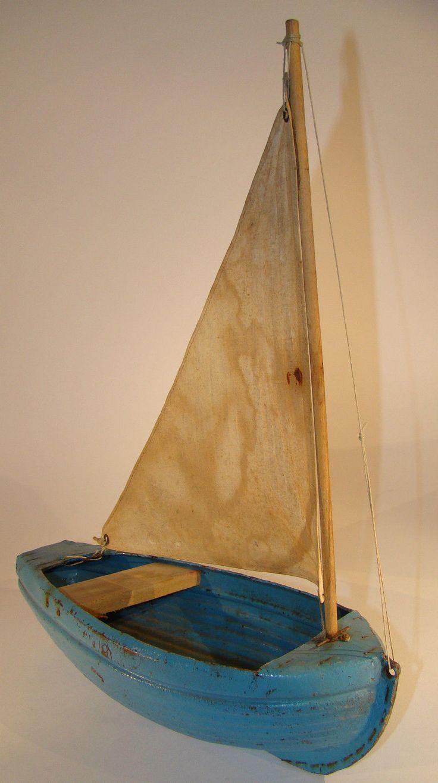 Voilier Agil produit par Gilaz, coque en carton bouilli, à clins C'est un Cat-Boat. Gréement rudimentaire, une simple voile triangulaire sur un mât de misaine sans haubans. Une banquette, pas de lest, l'équilibre est obtenu par un apport de matière à transporter (sable, cailloux, etc.). Longueur hors tout : 27 cm