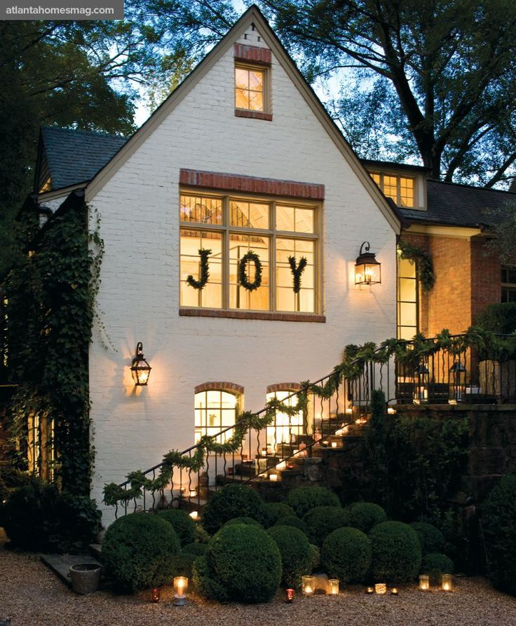 Aglow with varying votives, a spherical-shaped boxwood garden frames the Brinsons' charming 1930s cottage near Buckhead's Duck Pond.