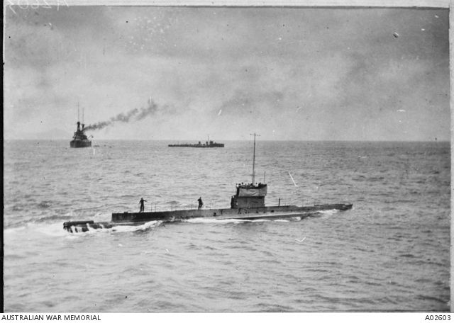 Royal Australian Navy submarine AE1 (foreground), HMAS Australia (left background) and a River class destroyer (centre background) at a rendezvous off Rossell Island before proceeding to Rabaul.  ...