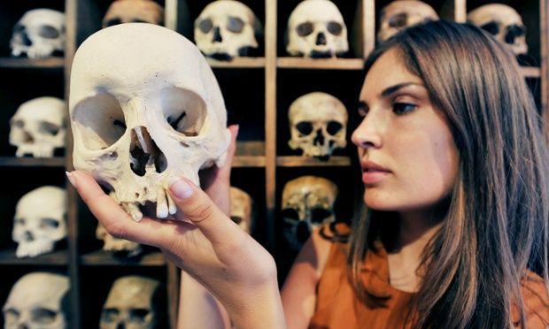 Marine Tanguy, gallery curator at the Outsiders Gallery in Soho, London, adjust 'Skulls' by the late Soho artist Sebastian Horsley