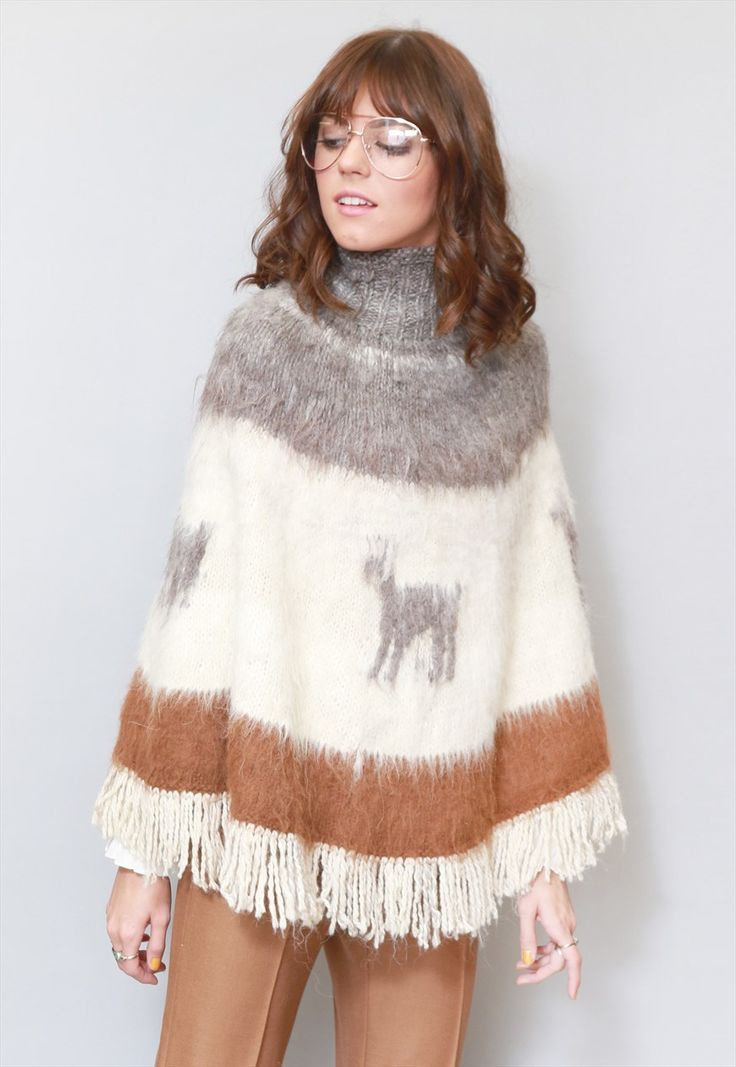 """Vintage 1970's Amerindia Alpaca Knit Cape.  Super trendy for this season, this cape will keep you cosy and warm! Roll neck. Features a pretty grey and brown knit alpacas and stripes. Gorgeous, thick, soft Alpaca wool. Cream tasseled edges. One Size. Please see the sizing section for measurements. Our model is a size 8. If you love Peekaboo Vintage, """"follow"""" us here on ASOS. First-time buyers will receive a discount code and you will also be kept up-to-date with our daily arrival..."""