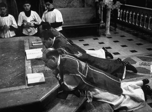 Priests prostrate themselves at foot of alter on Good Friday; March 1953, Poughkeepsie, NY