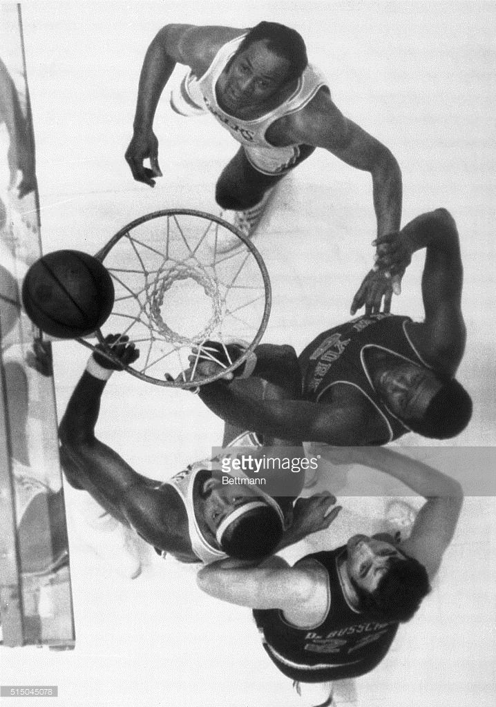 Elgin Baylor and Wilt Chamberlain of the Lakers and Willis Reed and Dave Debusschere of the Knicks all watch the ball bounce on the rim and fall in on a Baylor shot. The New York Knicks defeated the Lakers 111-108 in overtime for a 2-1 lead in the NBA Playoff Finals.
