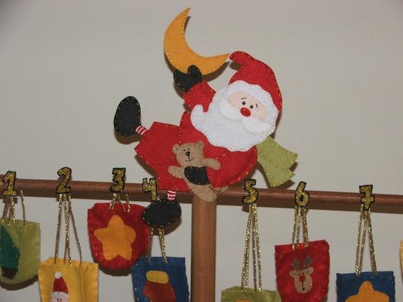Essa árvore vai deixar seus filhos encantados! Ela tem um lindo Papai Noel no topo e várias sacolinhas, uma para cada dia do mês de dezembro, sendo que todas são numeradas. A cada dia de dezembro, você coloca uma pequena lembrancinha para a criança (como uma bala, um chocolate, um brinquedinho...) no saquinho correspondente ao dia e assim ela vai fazendo a contagem regressiva até a chegada do Papai Noel!! Seu filho(a) vai adorar!! A coloração da madeira pode variar de peça para peça. Não…
